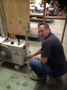 Chris learning the intricacies of installing air-conditioning